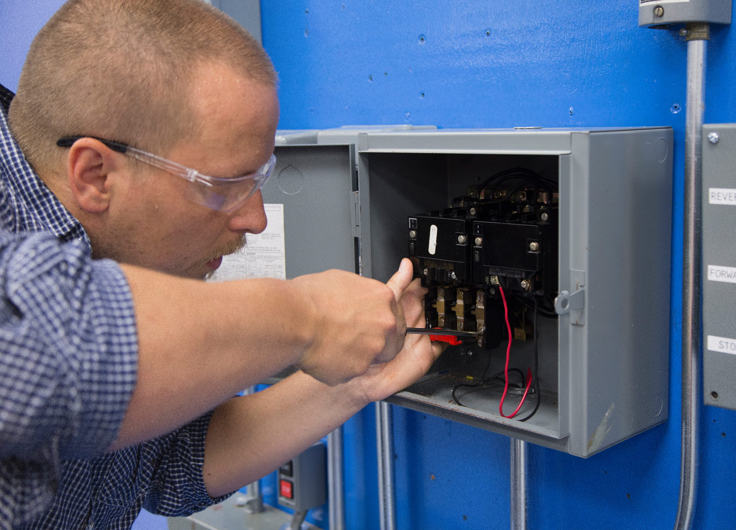 Electrical Engineering Technician student working on a panel